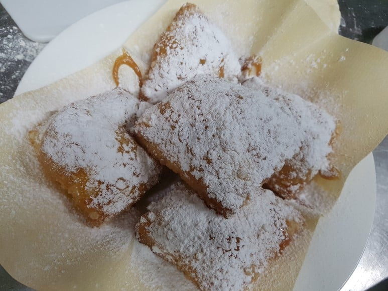 a plate of beignet with a light dusting of sugar on top dessert