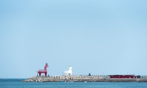 ihotewoo lighthouse in jeju island with a red horse statue and a white horse statue on a dock